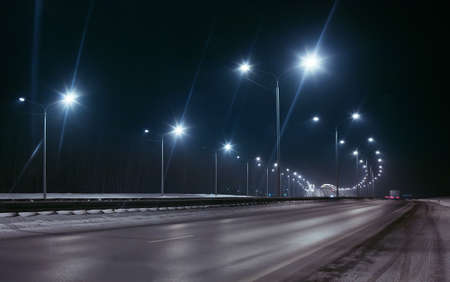 winter highway at night shined with lamps Standard-Bild
