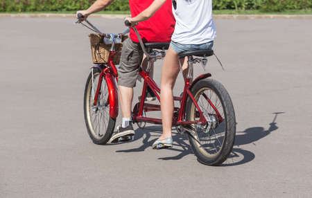 tandem bicycle: man and woman riding on a tandem bike close-up