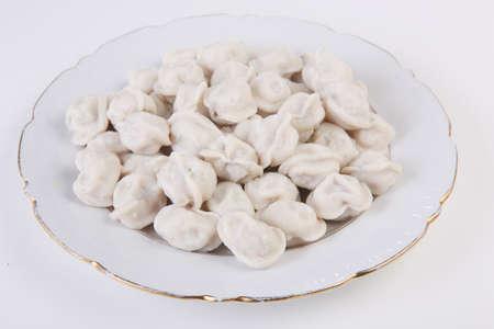 Russian pelmeni in white plate on white background