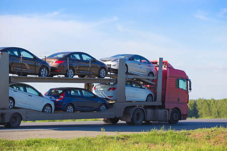 transportation of car on semi-trailer on country highway 스톡 콘텐츠