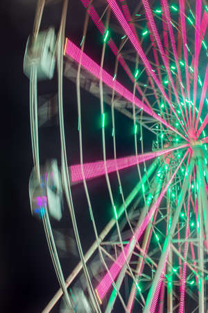 wheel spin: Carnival ride showing a spinning ferris wheel in action- long exposure shot Stock Photo