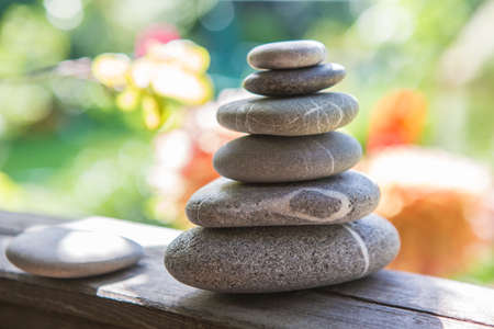 Balance of pebbles against the background of a flowering garden Stock Photo