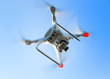 flying drone with camera in blue sky Stock Photo