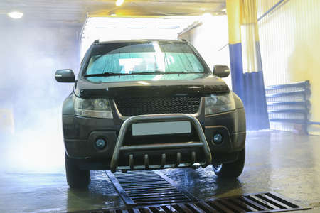 Car wash under stream of water Stock Photo