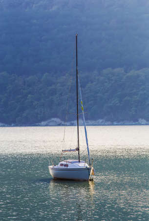Sailing yacht on beautiful lake amidst wooded mountains Stock Photo
