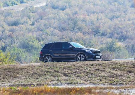 Modern SUV rides on a suburban highway Stock Photo