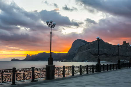 Crimean Black Sea embankment at sunset in the city of Sudak