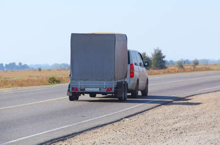 car with the trailer goes on country highway