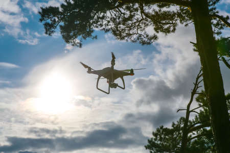 Flying drone with camera in blue sky background