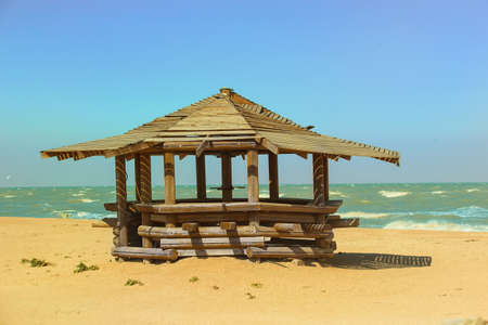 landscape with a wooden pergola on the sandy beach of the sea