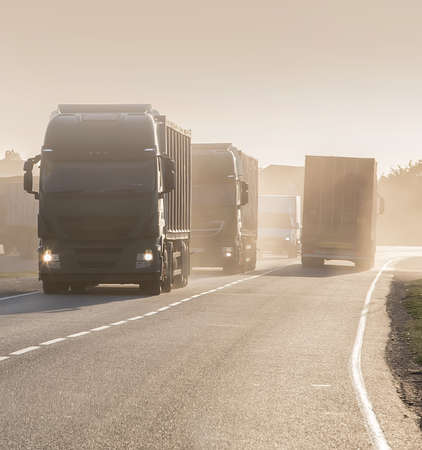 Column of trucks moves on a road. Stock Photo