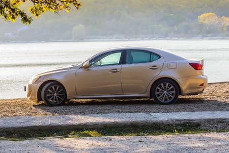 Beige prestige car on the lake shore in the fall