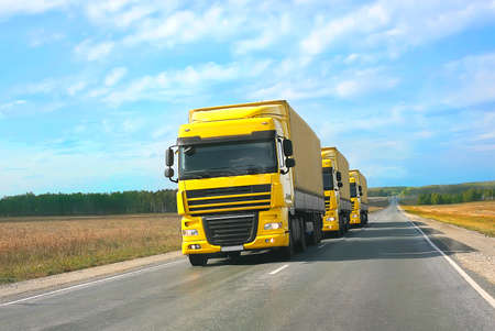 escort of yellow trucks on country road