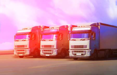 three trucks go on wide highway