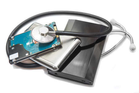 external hard drives and stethoscope on white background closeup