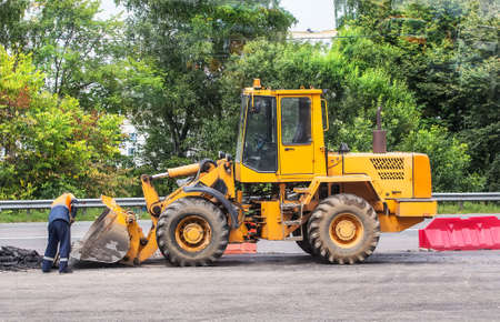 yellow forklift on road works on the highway in the city Stock Photo