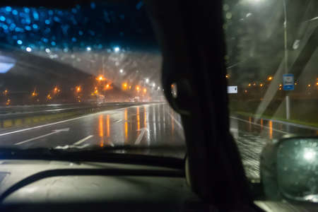 view from a driving car on a wet night highway
