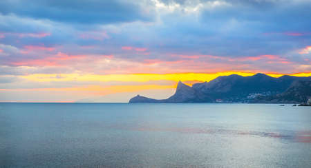 Colorful sunset in the sea bay. Mountainous background. Stock Photo