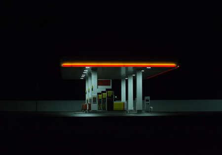 Illuminated gas station at night. Isolated on dark background.