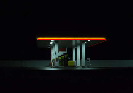Illuminated gas station at night. Isolated on dark background.