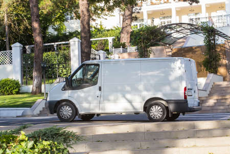 White van is parked in shade of trees on pavement at entrance to sanatorium surrounded by white fence.