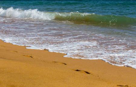 Sea waves roll on to shore. Sea foam. Traces of human feet. Closeup. 版權商用圖片