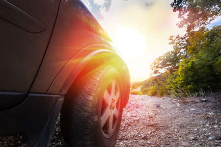 SUV rides on a mountain dirt road at sunrise close-up Stock Photo