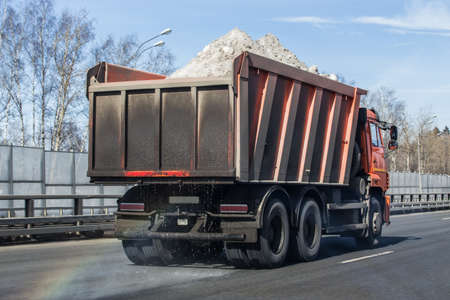 dump truck transports snow on the highway in the spring