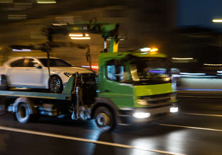 transportation of the car on the tow truck in the city at night. Blurred motion