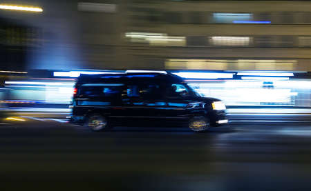 black minivan moves through the night Avenue. Blurred motion