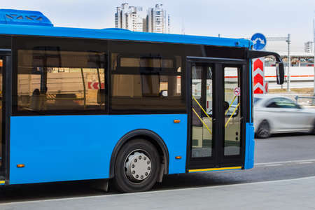 Blue city bus goes along street