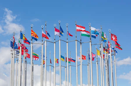 Flags of European states on flagpoles against the background of a cloudy sky.