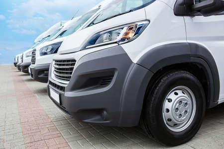 Anzahl neuer weißer Kleinbusse und Lieferwagen draußen