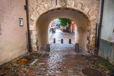 old cobbled street and house with arch in the center of Riga, Latvia. Editorial