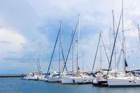 sailboats are moored on a pier on the seashore Editorial