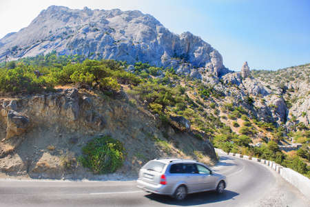 Car Moves along a winding road in the mountains during the day Stock Photo
