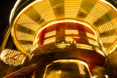 rotating lighted children's merry-go-round at night. Blurred motion Фото со стока