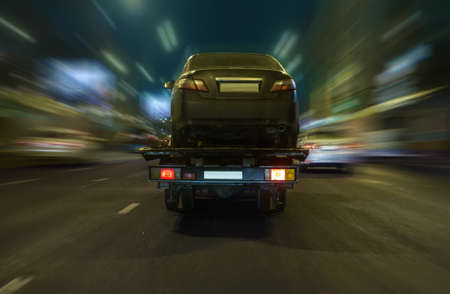 tow truck transports the car on the night street Stock Photo
