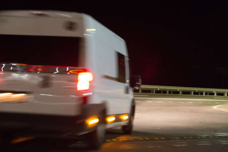 Minibus moving on a country highway at night. Blurred motion