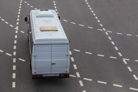 white minibus goes on the city street