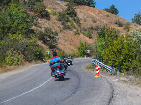 Bikers on motorcycles ride on a winding mountain road