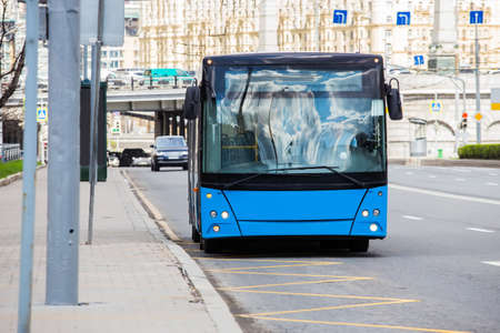 Bus moves to a stop on the street in the city center.