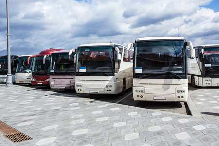 tourist buses on parking on the background of cloudy sky Фото со стока