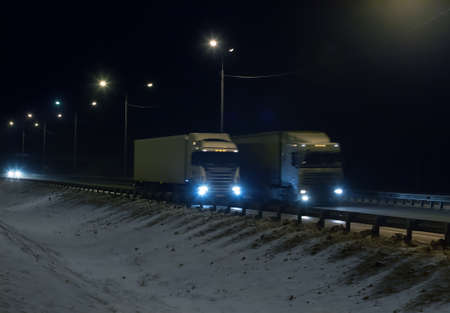 Trucks is moving along the winter road at night 免版税图像