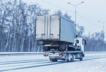 Car tow truck transports a broken truck along a winter road Stock Photo