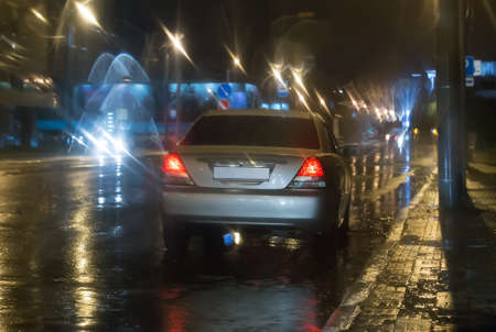 Car on the night wet lighted road in the rain in the city