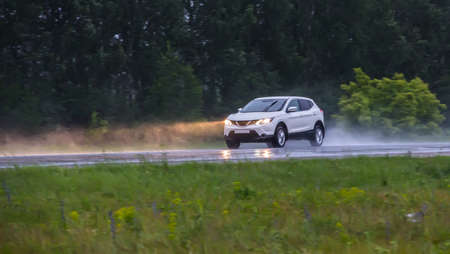car is moving on a wet road in the rain along the forest
