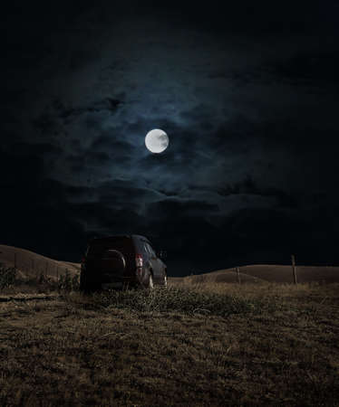 SUV is moving on a hilly terrain on a moonlit night Stock Photo