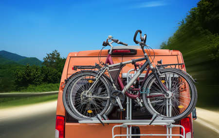 bicycles on the trunk of a minivan moving on a road