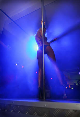 Striptease in night club. Caucasian girl in the spotlight in a swimsuit, heels, on stage with a pole, rear view